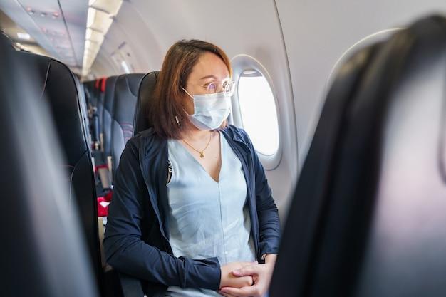 마스크를 착용 한 여성이 공항, 코로나 19 이후 새로운 라이프 스타일 여행으로 여행 중입니다. 사회적 거리두기 및 여행 거품 개념.