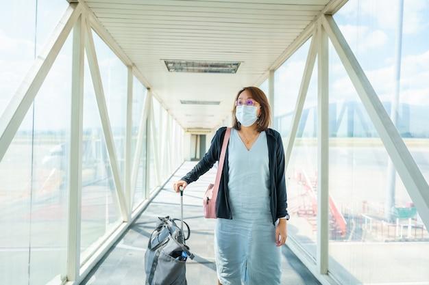 Женщина в маске путешествует по аэропорту, путешествие по новому образу жизни после covid-19. социальное дистанцирование и концепция пузыря путешествий.