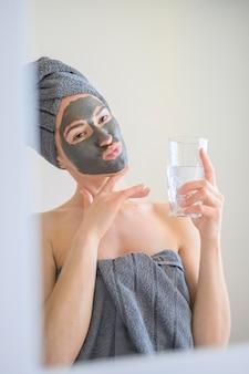 鏡で顔を作るフェイスマスクを着ている女性