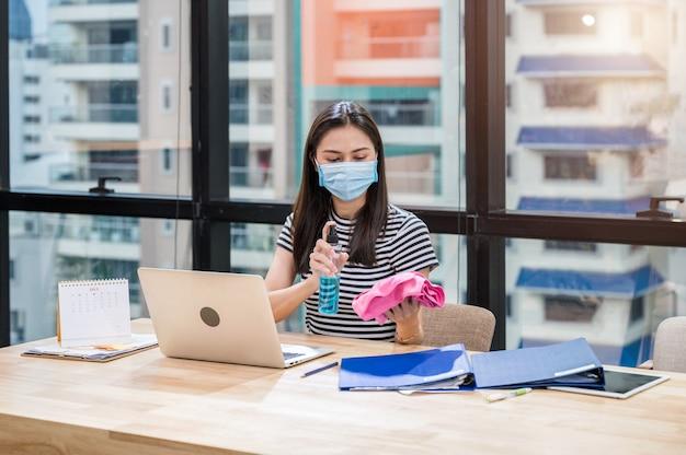 Женщина в маске для лица готовит спиртовой спрей и ткань для очистки на деревянном столе в офисе