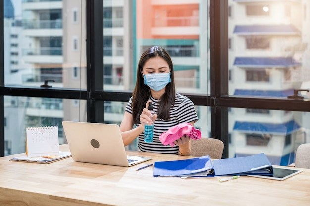 Woman wearing face mask preparing alcohol spray and cloth for cleaning on wooden desk in the office