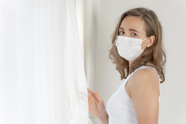 Woman wearing face mask to protect  feeling sick headache and cough because of coronavirus covid-19 in quarantine room