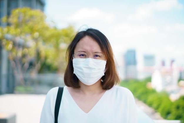 Женщина в маске защищает фильтр от загрязнения воздуха (pm2,5) или надевает маску n95. защитите загрязнение, анти смог и вирусы, загрязнение воздуха вызвало проблемы со здоровьем. концепция загрязнения окружающей среды.