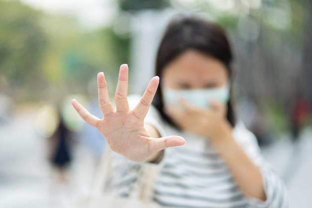フェイスマスクを着用している女性は、フィルターを大気汚染(pm2.5)から保護するか、n95マスクを着用します。汚染を保護し、