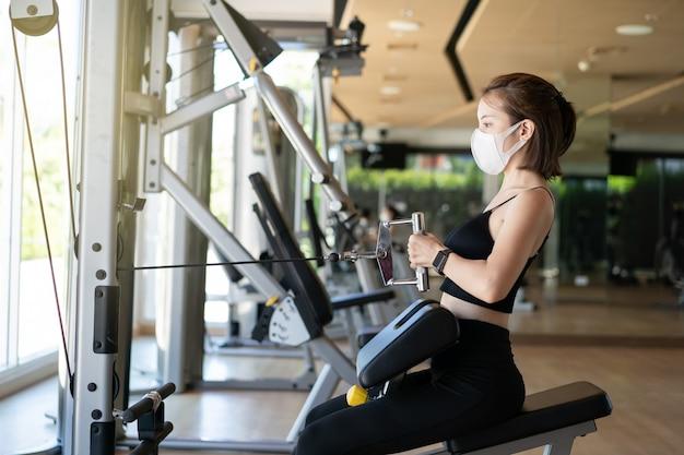 Женщина в маске сидела в ряду кабеля, потянув за кабель тренировки на гребном тренажере в тренажерном зале.