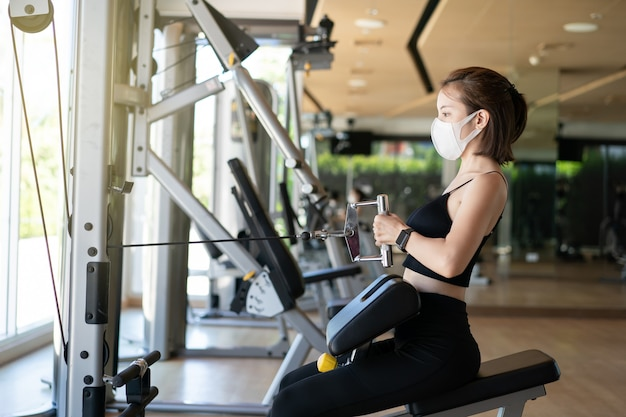 Woman wearing face mask seated cable row, pulling cable of rowing machine training in gym.