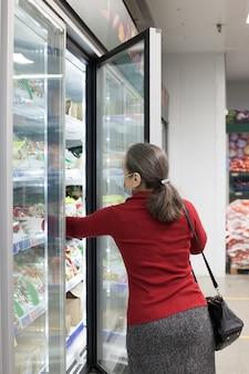 Женщина в маске для лица делает покупки и выбирает продукты в супермаркете, активные пожилые люди на пенсии