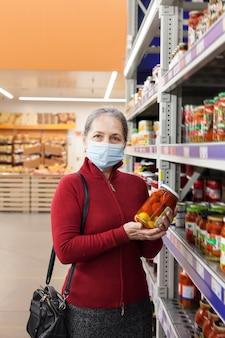 Женщина в маске для лица делает покупки и выбирает продукты в супермаркете