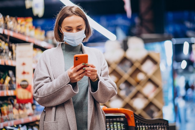 Woman wearing face mask and shopping in grocery store