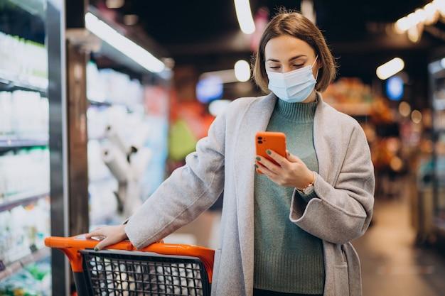 Donna che indossa la maschera per il viso e lo shopping nel negozio di alimentari