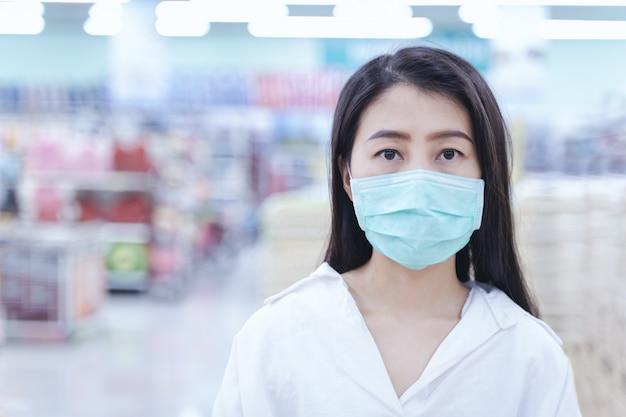 Женщина в маске для покупок в супермаркете