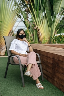 Woman wearing a face mask sitting on a chair beside a swimming pool in the garden.