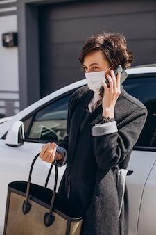 車のそばに立つフェイスマスクを着た女性 Premium写真