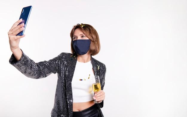 自撮り写真を撮るフェイスマスクを身に着けている女性