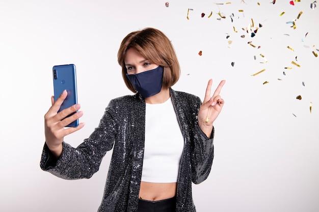 Woman wearing face mask taking a selfie