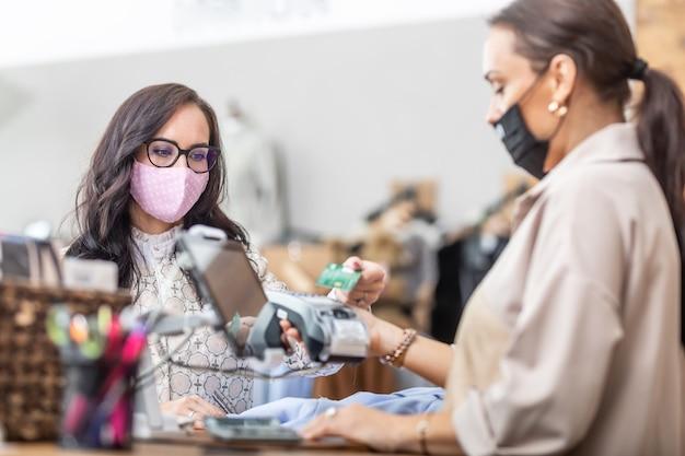 店内でフェイスマスクを適切に着用している女性は、口のすぐ上にフェイスマスクを着用しているショッピングアシスタントに非接触で支払います。