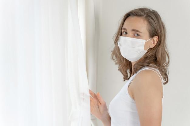 検疫室でコロナウイルスcovid-19のために気分が悪い頭痛と咳を保護するためにフェイスマスクを身に着けている女性