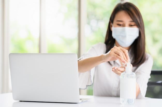 Женщина в маске для лица, используя спиртовой гель для мытья рук