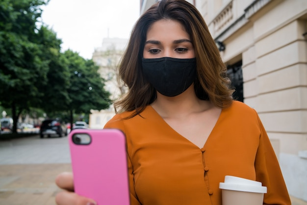 Woman wearing face mask and using her mobile phone while standing outdoors on the street. new normal lifestyle concept.