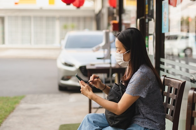 レストランの外でテイクアウトを待っている携帯電話を使用してフェイスマスクを着用している女性。