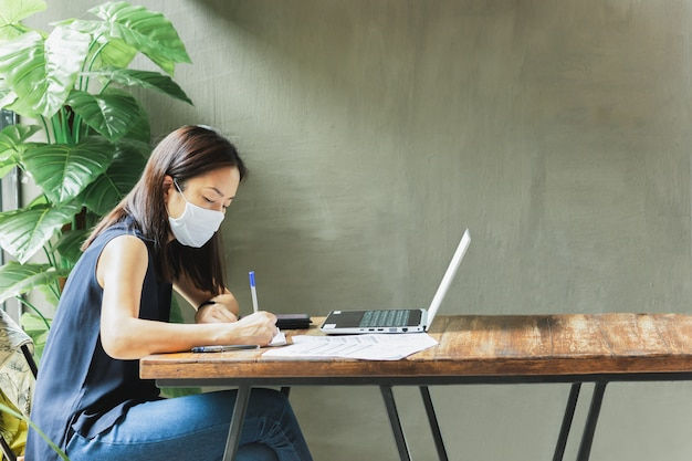 Woman wearing face mask working on paperwork with open laptop.