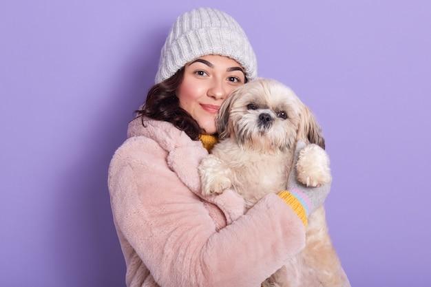 彼女のかわいい子犬を抱き締めるフェイクファーコートと暖かい白い帽子を着ている女性