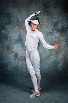 The woman wearing fencing suit with sword against gray