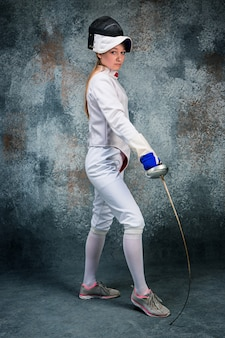 The woman wearing fencing suit with sword