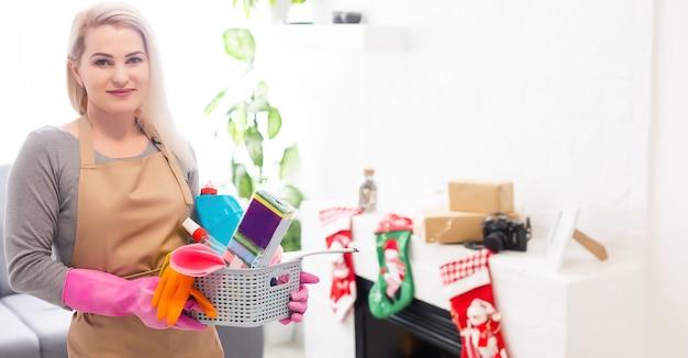 크리스마스 후 청소할 준비가 된 축제 장식을 입은 여성
