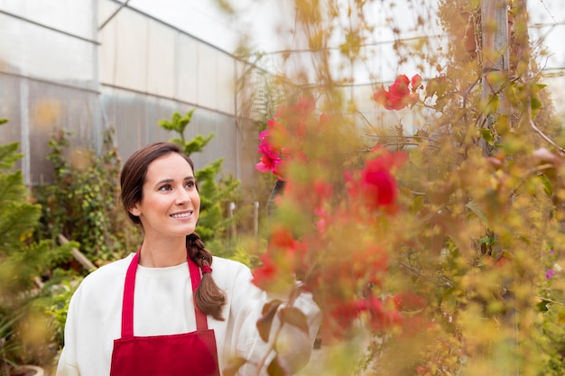 Woman wearing gardening clothes and admiring flowers in greenhouse