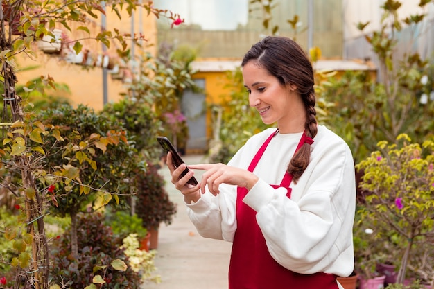 Woman wearing gardening clothes and holding phone in greenhouse