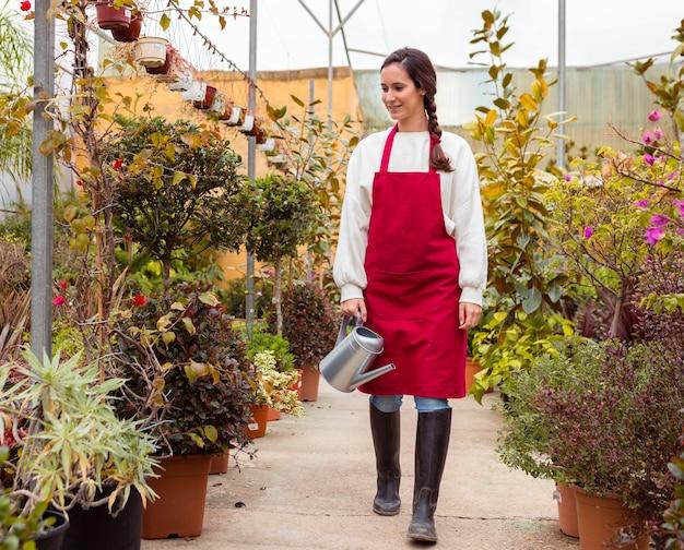 Woman wearing gardening clothes walking in greenhouse