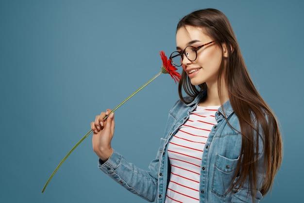 Женщина в очках с красным цветком возле лица модная студия