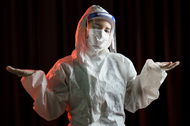 Woman wearing gloves, biohazard protective suit, face shield and mask. for corona virus or covid-19 protection.