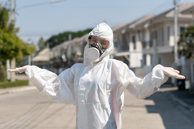 Woman wearing gloves with biohazard chemical protective suit and mask, no idea sign, no problem sign.
