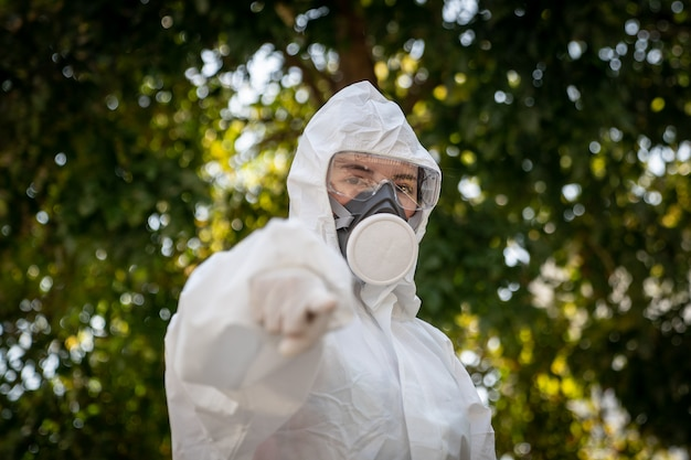 Woman wearing gloves with biohazard chemical protective suit and mask. pointing finger at you.