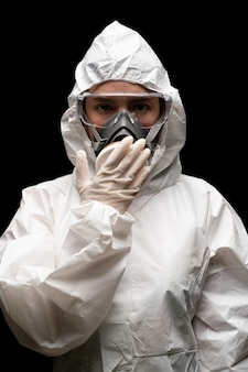 Woman wearing gloves with biohazard chemical protective suit and mask. shocked impressed, covering mouth with hands .