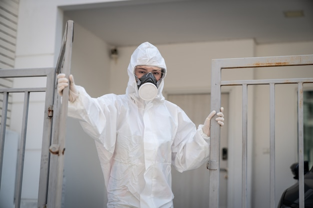 Woman wearing gloves with biohazard chemical protective suit and mask.with unhappy face. opening an iron gate.