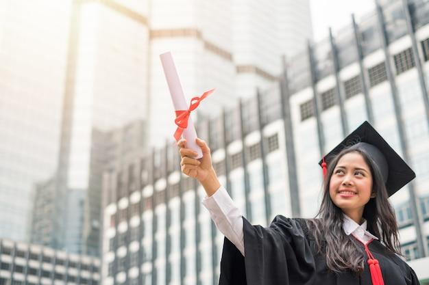 Женщина в платье с успехом поднимает руку, степень бакалавра университета