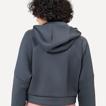 Woman wearing gray hoodie for winter fashion studio shoot rear view