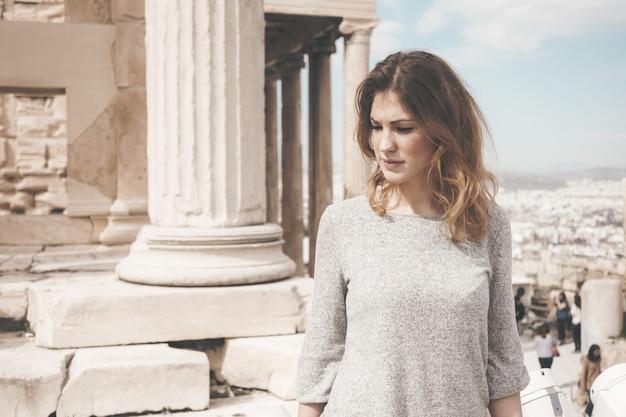 昼間に白いコンクリートの柱の横に立っている灰色の長袖ブラウスを着ている女性