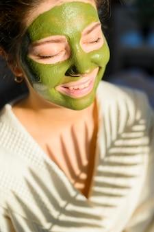 Женщина носит зеленую маску