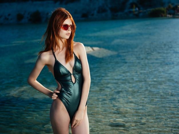 余暇のライフスタイルをポーズする緑の水着サングラスを着ている女性