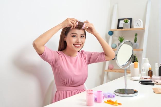 Женщина в бигуди смотрит в зеркало с широкой улыбкой