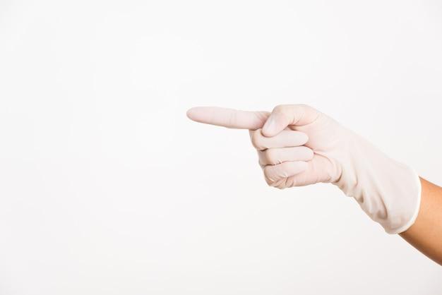 Женщина, держащая руку на белой резиновой латексной хирургической медицинской перчатке для врача с жестом указывая пальцем