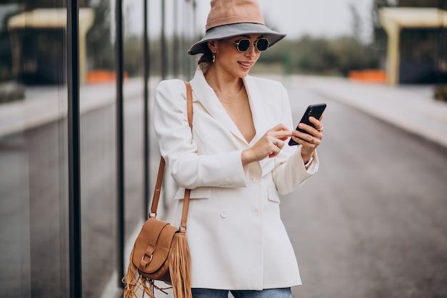 帽子をかぶって、通りの外で電話を使用している女性