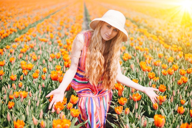 Woman wearing a hat and a colorful dress in a orange tulips field with bright sunlight