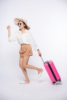 Donna che indossa un cappello, occhiali e manici di valigie per viaggiare