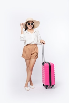 Woman wearing a hat, glasses, and handles of suitcases to travel