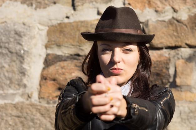 カメラに向かって拳の手振りを作る帽子をかぶった女性